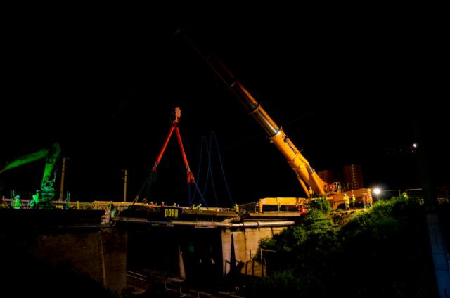 Kran, Porr, Baustelle mit Arbeitern in der Nacht